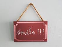 Hölzernes Tag gemalte Aufschrift: Lächeln Stockfotos