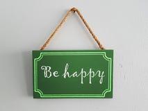Hölzernes Tag gemalte Aufschrift: seien Sie glücklich Stockbild