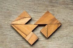 Hölzernes Tangrampuzzlespiel im unterschiedlichen Herzformhintergrund Lizenzfreie Stockfotos