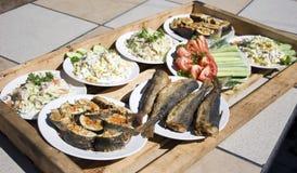 Hölzernes Tellersegment mit Fischen und Salat Stockfoto