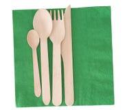 Hölzernes Tischbesteck, Messergabel und Löffel, auf Grünbuchserviette, Serviette, lokalisiert auf Weiß Lizenzfreies Stockfoto