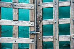 Hölzernes Tor der Alten Welt vor grünen Türen Stockfoto