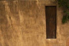 Hölzernes Tor in einem Adobe-Zaun mit einem Sicherheits-Fenster, Santa Fe, Lizenzfreies Stockbild