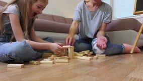 Hölzernes Turmspiel des glücklichen Familienspiels stock video footage