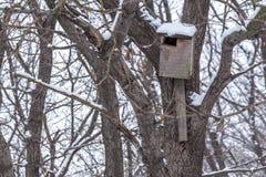 Hölzernes Vogelhaus, das am Baum im Winterwald hängt Lizenzfreie Stockfotos