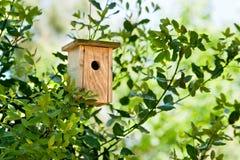 Hölzernes Vogelhaus, das im Baum hängt Lizenzfreie Stockbilder