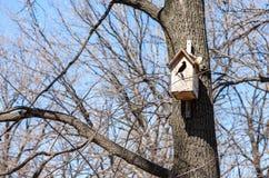 Hölzernes Vogelhaus, das von einem Baum hängt Lizenzfreies Stockfoto