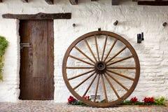 Hölzernes Wagenrad und Tür im andalusischen Patio Stockfotos