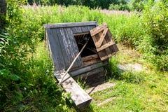 Hölzernes Wasser des Dorfs gut mit der offenen Tür und einem Blecheimer Stockfotos