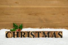 Hölzernes Weihnachtswort mit Stechpalme und Schnee Lizenzfreie Stockbilder