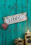 Hölzernes Willkommensschild mit rotem Herzen und brennenden den Kerzen, die am antiken Knickentenblau hängen, verwitterte Zaun Lizenzfreies Stockbild