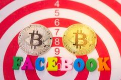 Hölzernes Wort Facebook und zwei Cryptocurrency bitcoin auf weißem Hintergrund Facebook und bitcoin stockfotografie