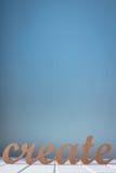 Hölzernes Wort schaffen gegen einen blauen Hintergrund Lizenzfreies Stockfoto