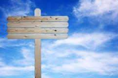Hölzernes Zeichen auf bewölktem blauem Himmel Stockfotografie