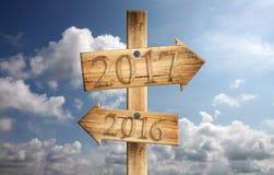 Hölzernes Zeichen von 2016 im links und von 2017 im Recht auf blauer Himmel backgrou Lizenzfreie Stockfotografie