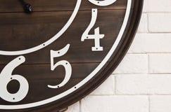 Hölzernes Zifferblatt auf weißer Wand Stockbild