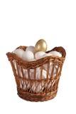 Hönaägg med guld- i en korg sköt arkivbild