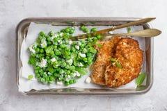 Höna- eller grisköttschnitzel med ost och ärtasallad arkivfoto