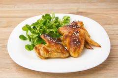 höna stekte vingar Fega vingar av en grillfest på en vit platta med sallad Royaltyfri Foto