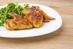 höna stekte vingar Fega vingar av en grillfest på en vit platta med sallad Arkivfoton