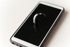 Hörapparat och hörlur Begrepp av utfrågningomsorg arkivbilder