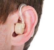 Hörapparat på mannens öra arkivbilder