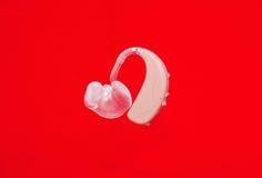 Hörapparat på rött Arkivfoto