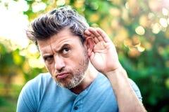 hören Schließen Sie oben an Hand und das Ohr, das auf einen ruhigen Ton O hört lizenzfreie stockfotos