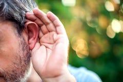 hören Schließen Sie oben an Hand und das Ohr, das auf einen ruhigen Ton O hört stockfotos