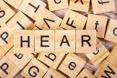 Hören Sie - Würfel mit Buchstaben, Zeichen mit hölzernen Würfeln Stockfotos