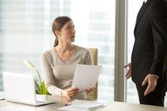 Hörende Ansprüche der jungen Frau an sie Arbeit vom Chef Lizenzfreie Stockfotos
