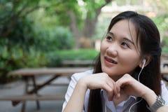 Hörende Musik der asiatischen Frau Stockfoto