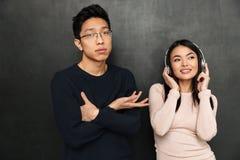 Hörende Musik der erfreuten sorglosen asiatischen Frau durch Kopfhörer Lizenzfreies Stockbild