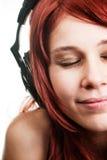 Hörende Musik der Frau an den Kopfhörern stockbild