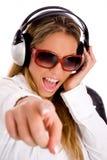 Hörende Musik der Frau und Zeigen auf camer Lizenzfreie Stockbilder