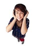 Hörende Musik der glücklichen jugendlich Frau Stockbilder