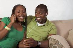 Hörende Musik der glücklichen jungen ethnischen schwarzen Paare Stockfotos