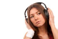 Hörende Musik der jungen Frau des Brunette in den Kopfhörern Lizenzfreie Stockfotos