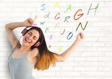 hörende Musik der jungen Frau mit Farbbuchstaben herum Lizenzfreies Stockbild