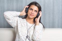 Hörende Musik der jungen Frau mit Kopfhörern im Raum zu Hause auf dem Sofa Stockfotografie