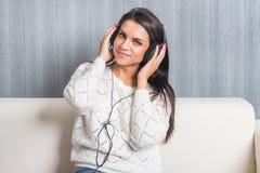 Hörende Musik der jungen Frau mit Kopfhörern im Raum zu Hause auf der Sofablickkamera Stockfoto