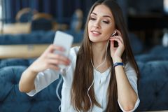 Hörende Musik der jungen Frau unter Verwendung ihres Smartphone Restaurantsitzung stockbilder