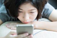 Hörende Musik der jungen Frau vom Handy lizenzfreies stockfoto