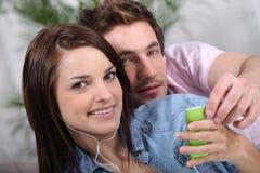 Hörende Musik der jungen Paare Lizenzfreies Stockfoto