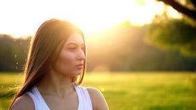 Hörende Musik der jungen Schönheit am Park beim Laufen Porträt des lächelnden sportlichen Mädchens mit dem Kopfhörer, der betrach stock video footage