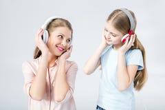 Hörende Musik der Mutter und der Tochter mit Kopfhörern im Studio stockfotos