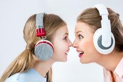 Hörende Musik der Mutter und der Tochter mit Kopfhörern im Studio stockbild