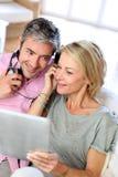 Hörende Musik der reifen Paare mit Tablette Lizenzfreie Stockfotos