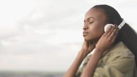 Hörende Musik der reizenden jungen Afroamerikanerfrau und Entspannung auf dem unscharfen Stadthintergrund stock video footage