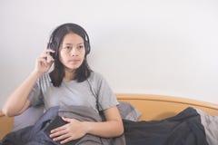 Hörende Musik der schönen Asiatin mit dem Kopfhörer, der auf dem Bett sich entspannt stockbild